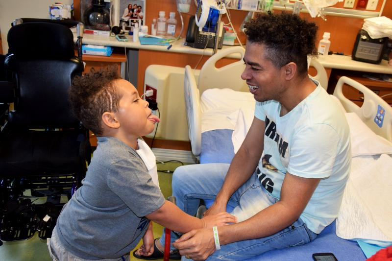 Elder and his father joke around while in his hospital room at Blythedale Children's Hospital.