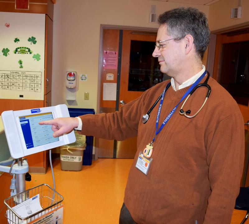 Dr. Byron Fernandez, Unit Chief of Blythedale's Pediatric and Adolescent Unit, utilizes a portable tablets to translate informat